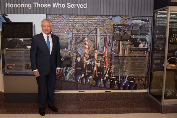 Former Secretary of Defense Chuck Hagel stands next to his quote in a hallway dedicated to veterans.