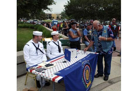 Navy servicemen distributed brochures and Vietnam pins for the Memorial Day ceremony