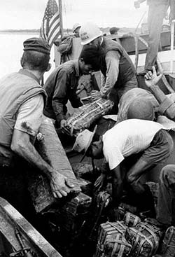 U.S. and South Vietnamese Personnel Unload Ammunition