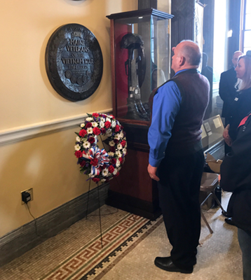 A visitor looks at Maine's State House wall plaque