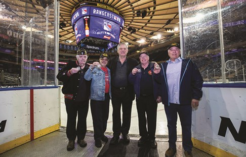New York Rangers hockey alum Ron Greschner stands with four Vietnam veterans honored at the game.