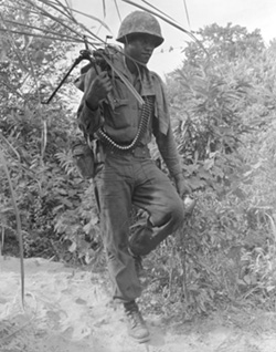 Marine Machine Gunner Carrying his Weapon
