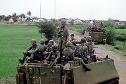 Vietnamese Popular Force soldiers riding on Australian APCs