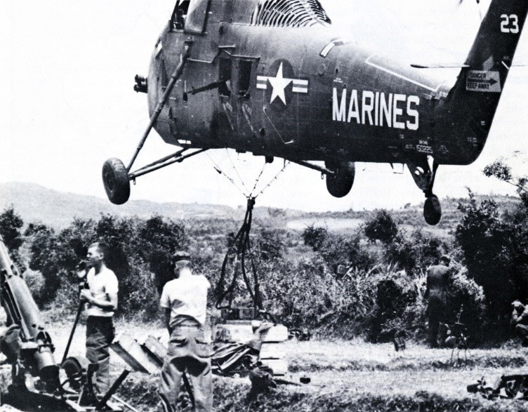 U.S. Marine Corps UH-34 helicoptors taking off with external cargo load, circa August 1965, during Operation STARLITE